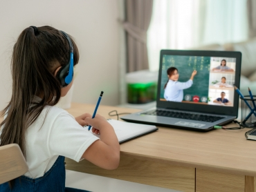 Asian girl student video conference e-learning with teacher and classmates on computer in living room at home. Homeschooling and distance learning ,online ,education and internet.